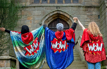 Three women holding hands, which are raised in the air. Viewed from the back, two are wearing headscarves and all wear shiny 'WOW' capes like superheroines
