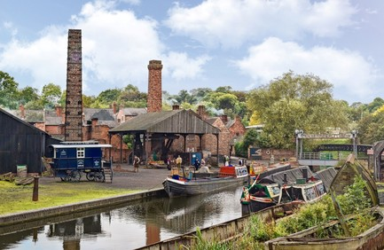 Canal with narrow boats in foreground, industrial chimneys behind