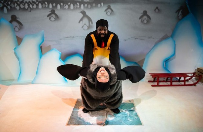 Icy backdrop with draw penguins; in front, two humans dressed as penguins look to camera – one's holding the others' 'wings' as they learn back and smile