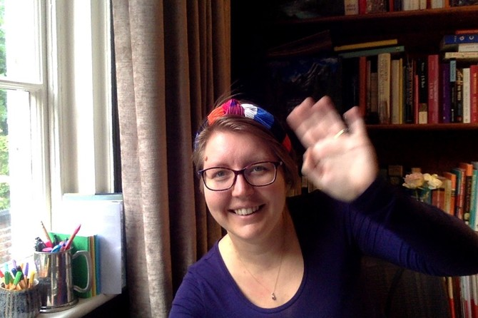 Natasha wears a colourful headscarf, dark-rimmed glasses and a blue long-sleeved top, and is smiling and waving at the camera