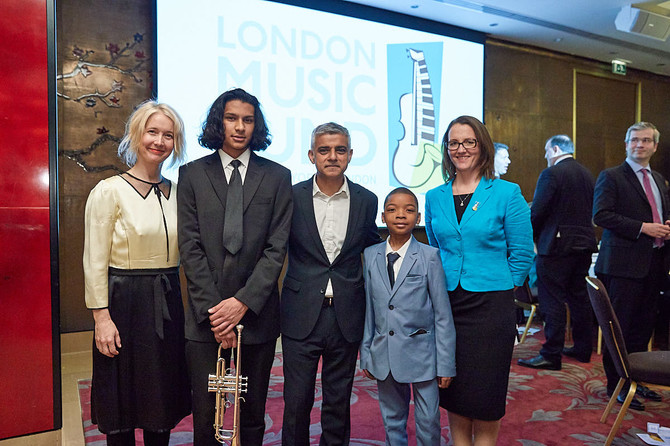 Five people stand in front of a large screen with Mondon Music Fund logo. At the centre is Lord Mayor of London, Sadiq Khan, and on the right Chrissy Kinsella, Chief Executive of London Music Fund