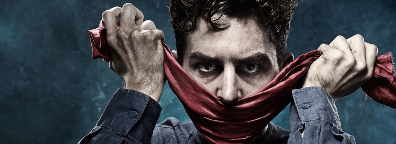 Show image for The Grinning Man: a man hold a crumpled red scarf in his fists, either side of face, so the scarf resembles an ominous 'smile'
