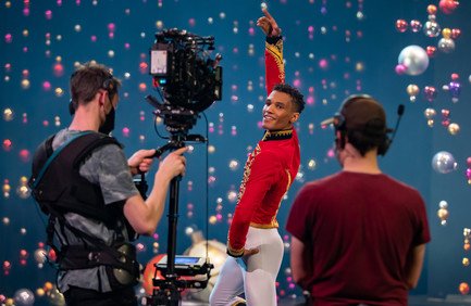 Scottish Ballet First Artist Jerome Anthony Barnes in 'nutcracker' soldier costume dances in front of a film camera and crew