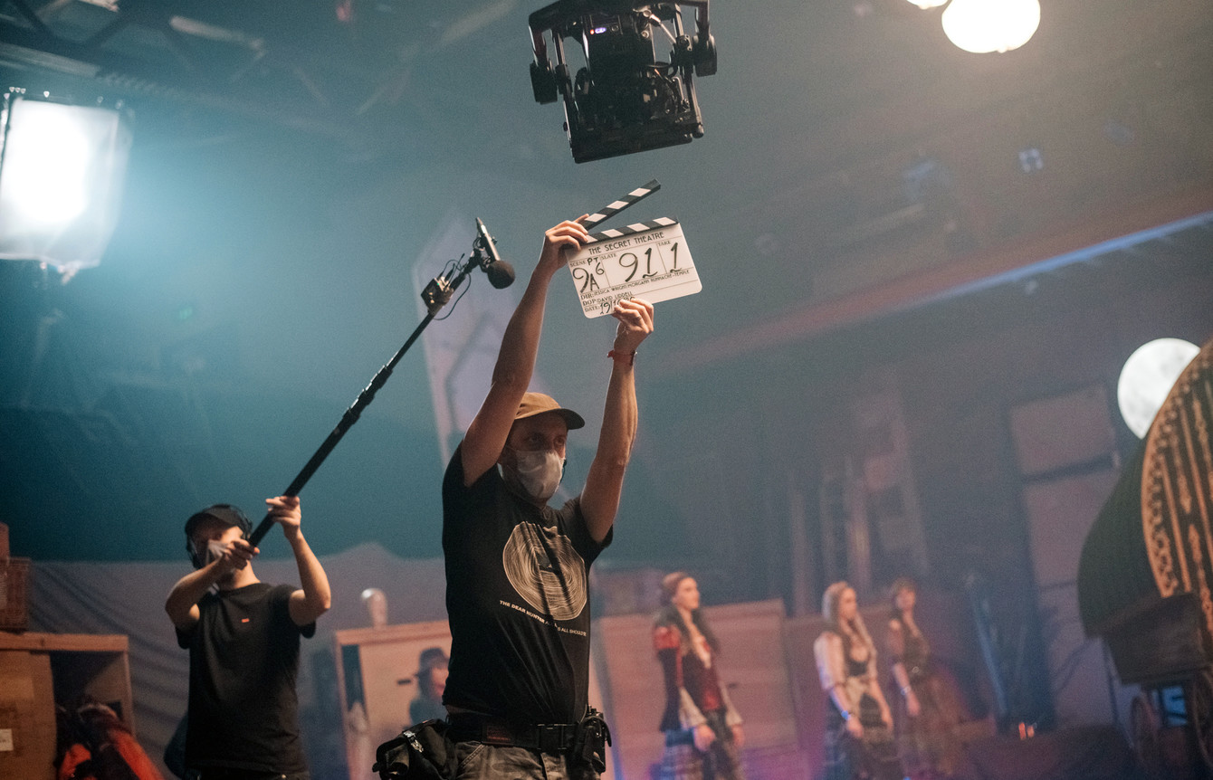 A film crew member holds a film slate aloft, while a boom operator stands behind them, and costumed cast members are poised in the background