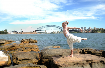 Dancer from Matthew Bourne's Swan Lake poses in costume, on the waters' edge – with Sydney Opera House in the background (from the 2013 Australian tour)