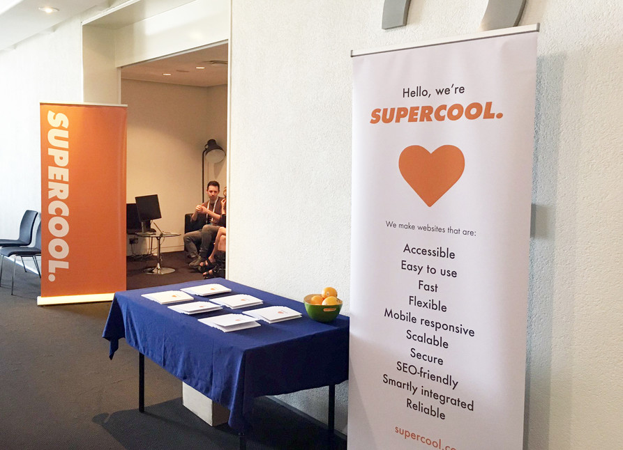 View from outside the Supercool Pod at AMAConf 2019. There're a couple of Supercool pull-up banners, a table with our 'Access Notebooks' and some oranges, and James is sat inside the pod running a session.