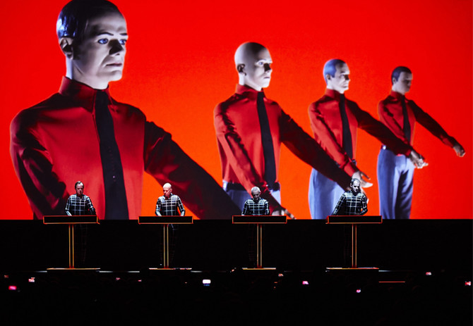 Image of Kraftwerk on stage, controlling huge graphics on the screen behind them