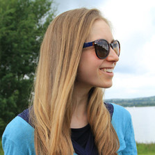 Headshot of Helen Shadock - Helen has long, strawberry blonde hair, and is wearing a blue top and sunglasses. She is turned to the right and is smiling